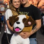 Young couple poses with large stuffed dog with fair lights in background.